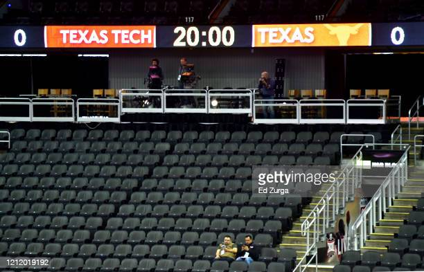 Two journalists sit in an empty Sprint Center after it was announced that the Big 12 basketball tournament had been cancelled due to growing concerns...