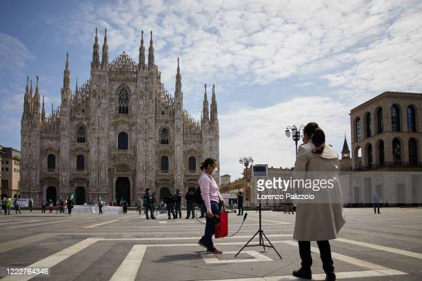 Two journalists wearing protective masks in front of the Milan Cathedral on the first day of the reopening of the city on May 04, 2020 in Milan,...