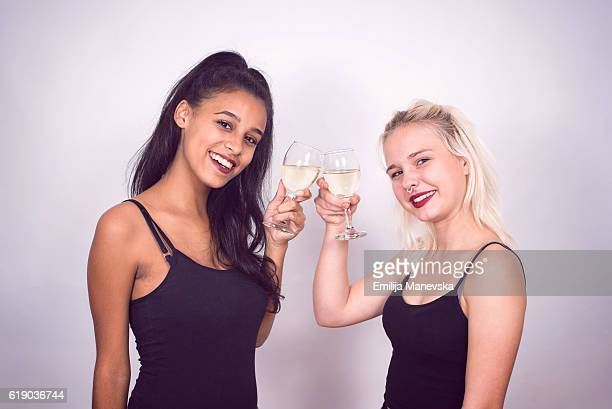 Two joyful pretty friends celebrating new year or birthday party, have fun, drink alcohol and dancing