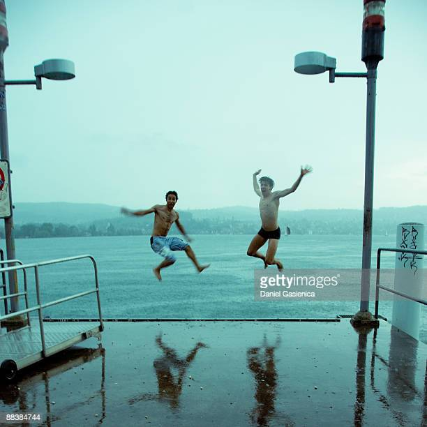 Two jumping into lake