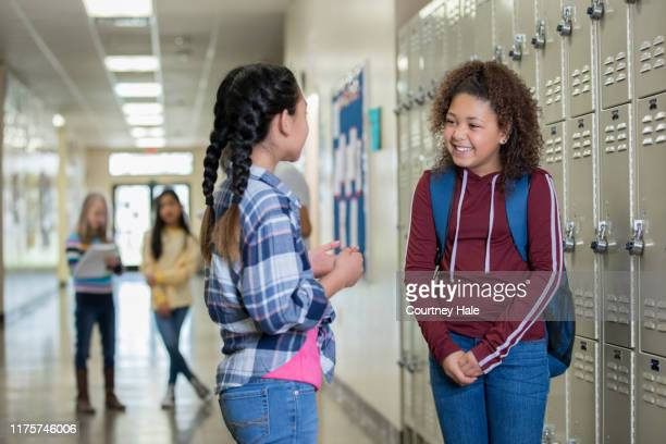 two junior high students laughing together in hallway - charter_school stock pictures, royalty-free photos & images