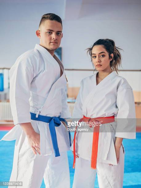 two karate students standing indoors - martial arts stock pictures, royalty-free photos & images