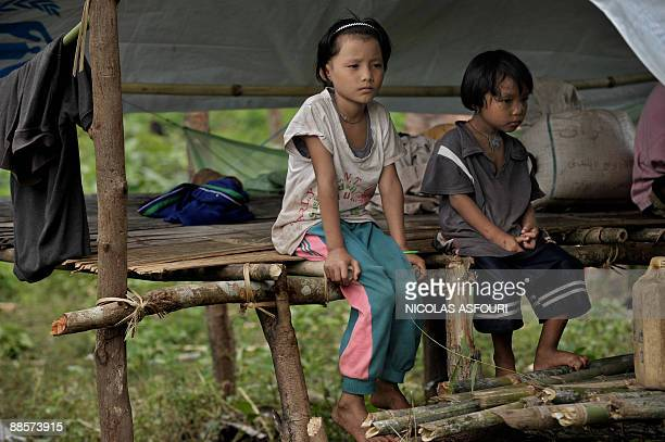 Two Karen refugee girls rest under a temporary shelter on the ThaiMyanmar border in Per Nwe Pu village around 100 km north of Mae Sot on June 17 2009...