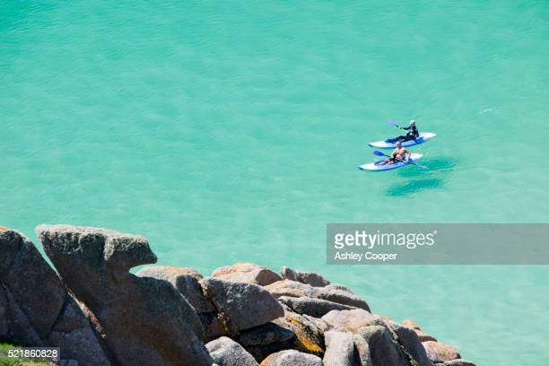 two kayakers at porthcurno bay, cornwall - porthcurno stock pictures, royalty-free photos & images