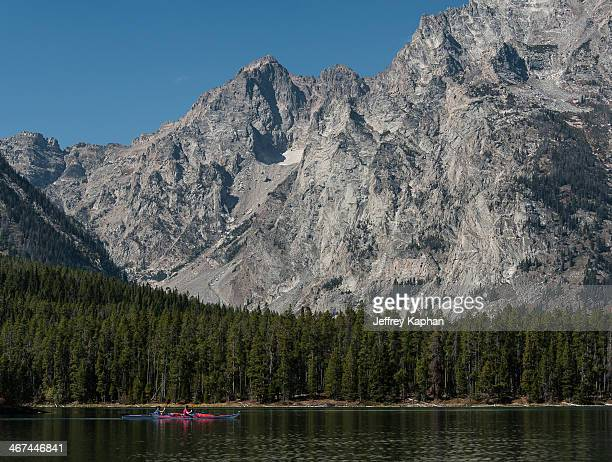 Two kayakers floating under the western ridge of Mt. Moran. On Leigh Lake in Grand Teton National Park, Wyoming.
