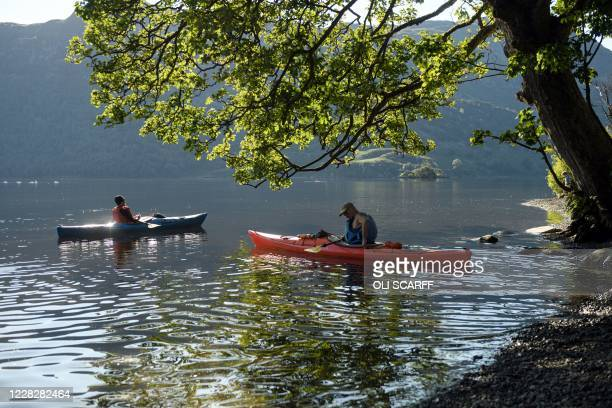 Two kayakers launch themselves into Ullswater in the sunshine near Glenridding in the Lake District in north west England on Bank Holiday Monday,...