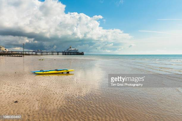 two kayaks on the beach and eastbourne pier at low tide - eastbourne stock pictures, royalty-free photos & images