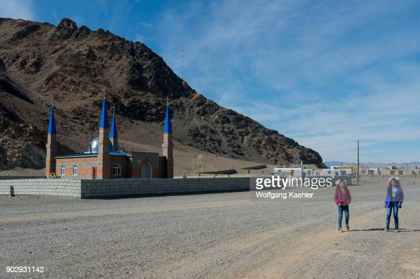 Two Kazakh girls walking along a street in front of a new mosque at the outskirts of the city of Ulgii in the BayanUlgii Province in western Mongolia