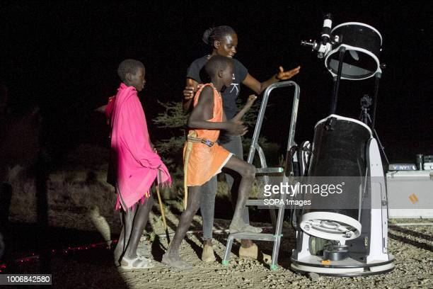 Two Kenyan Boys seen heading for the telescope People witness the Lunar Eclipse in Oloika Town Magadi Kenya The Moon completely covered the Earth's...