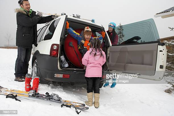 Two kids are playing while their parents collect the ski gear.