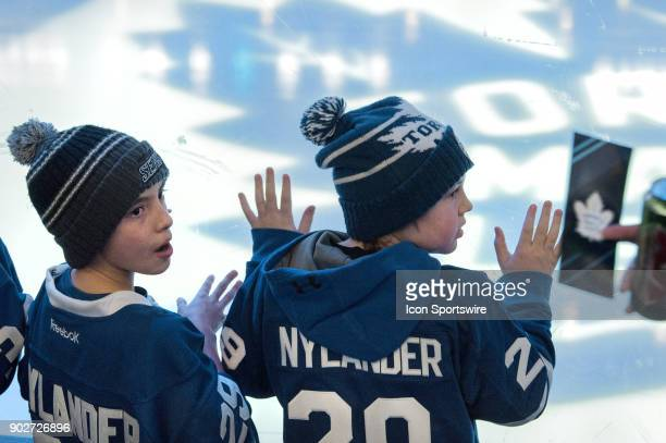 Two kids both wearing Left Centre William Nylander Jerseys are temporarily distracted from the light show before the game as a fan with Platinum...