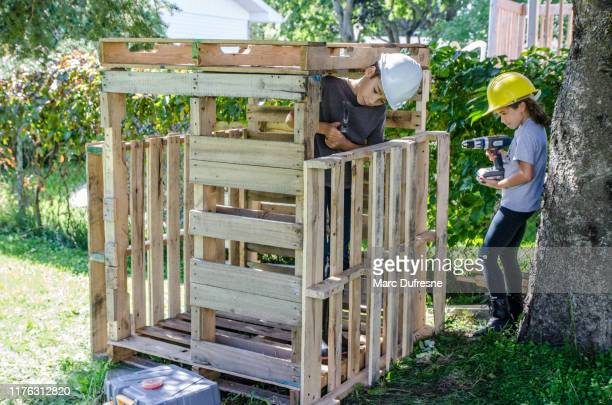 two kids building a wooden shack - hut stock pictures, royalty-free photos & images