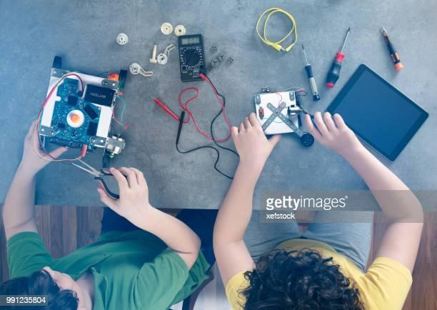 Zwei Kinder baut einen Roboter.