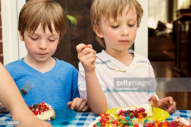 Two kids eating candy covered birthday cake at outdoors party.