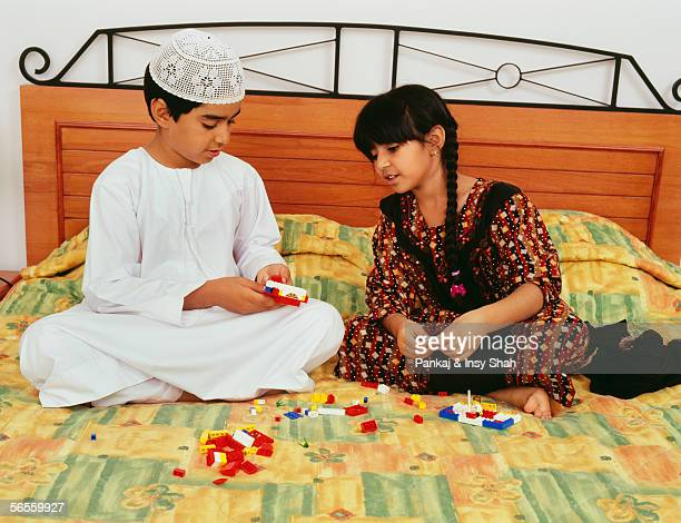 Two kids enjoying themselves as they play on the bed.