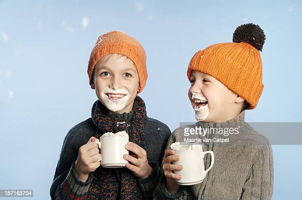 Two kids having fun in the snow drinking hot chocolate