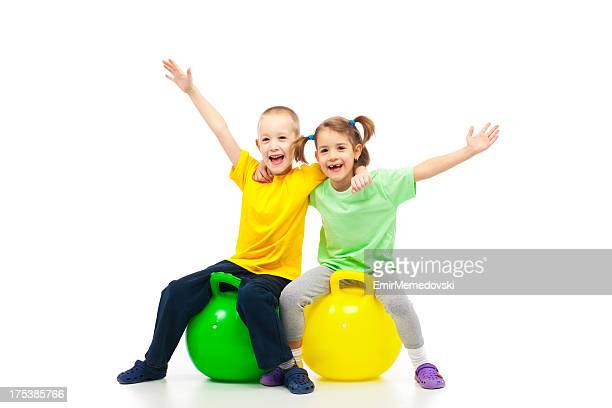 two kids heaving fun with bouncing ball - bouncing ball stock photos and pictures