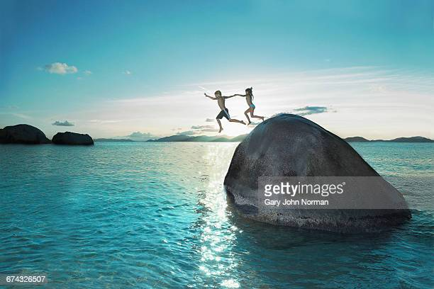 two kids holding hands jumping off rock into sea - nature stock pictures, royalty-free photos & images