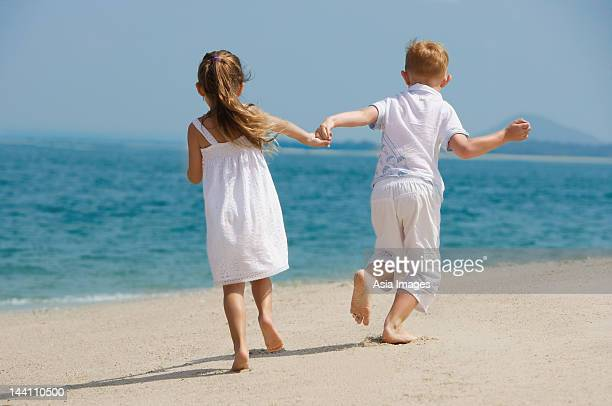 two kids holding hands on beach