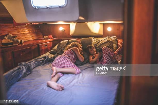 zwei kinder im hauptanlegeplatz eines segelbootes entspannen - wohngebäude innenansicht stock-fotos und bilder