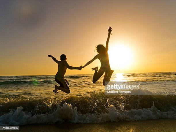 two kids jump into ocean at sunset