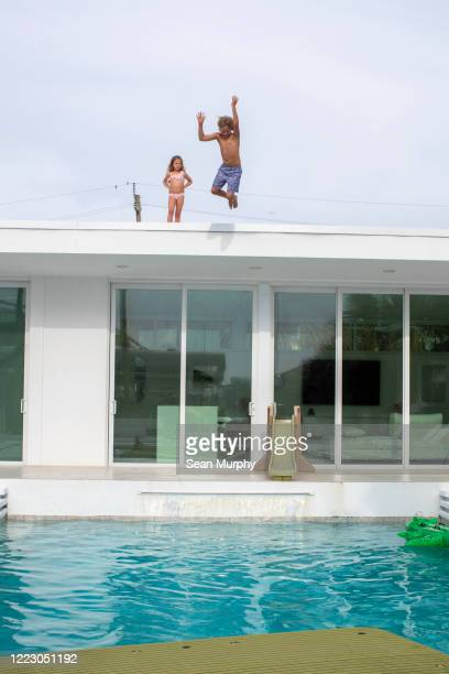 two kids on a roof.  young boy jumping into pool while girl watches. - naughty america stock pictures, royalty-free photos & images