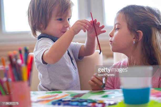 two kids painting togeder