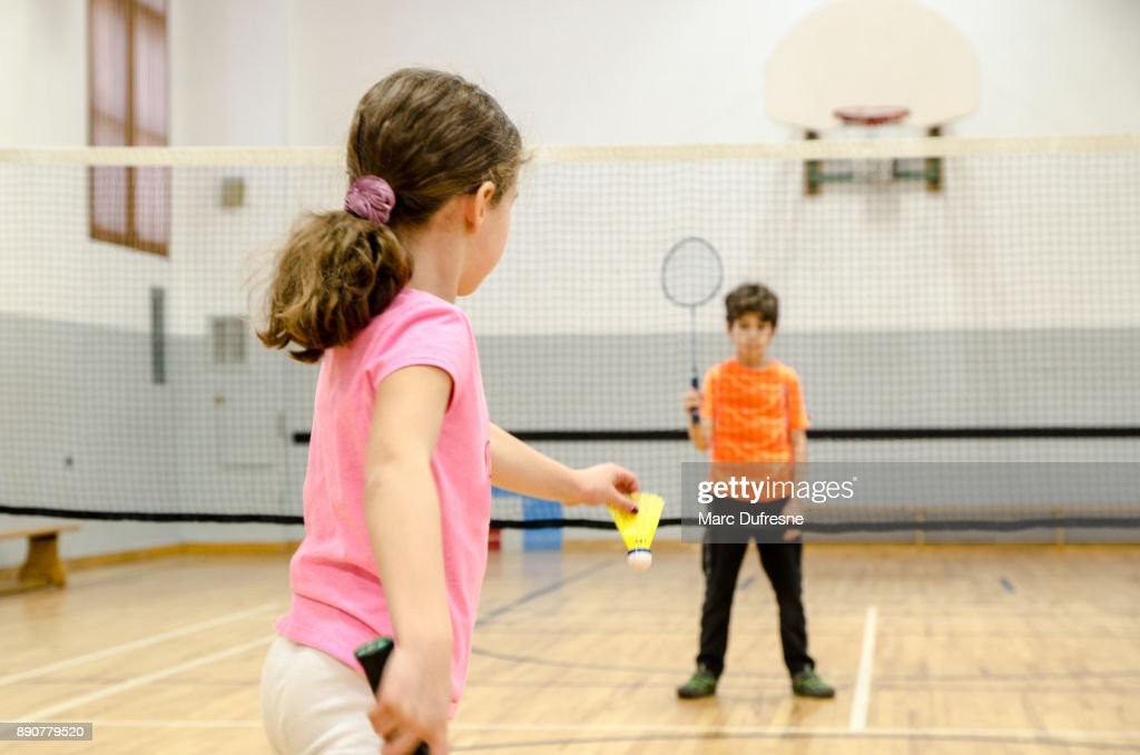 Two kids playing badminton in a gymnasium : Stock Photo
