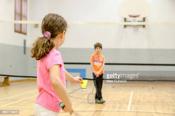 two kids playing badminton in a gymnasium - badminton stock photos and pictures