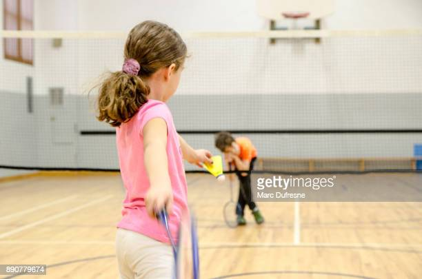 Two kids playing badminton in a gymnasium