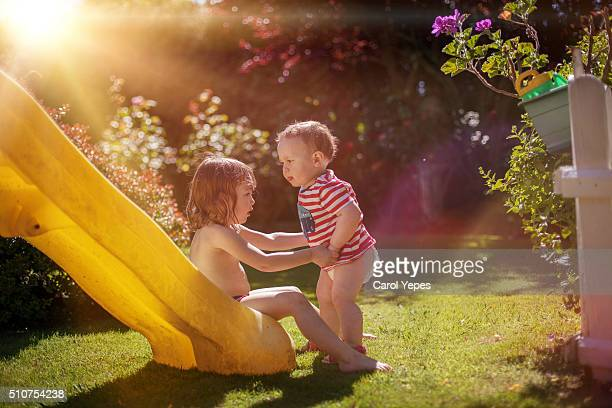 two kids playing on slide - diaper boy stock photos and pictures