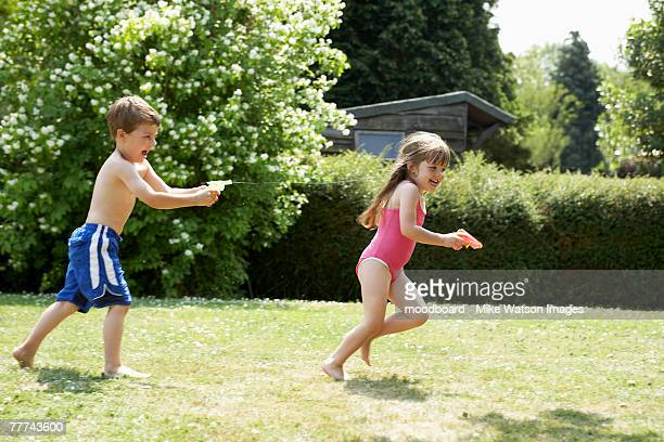 two kids playing with squirt guns - maillot de bain photos et images de collection