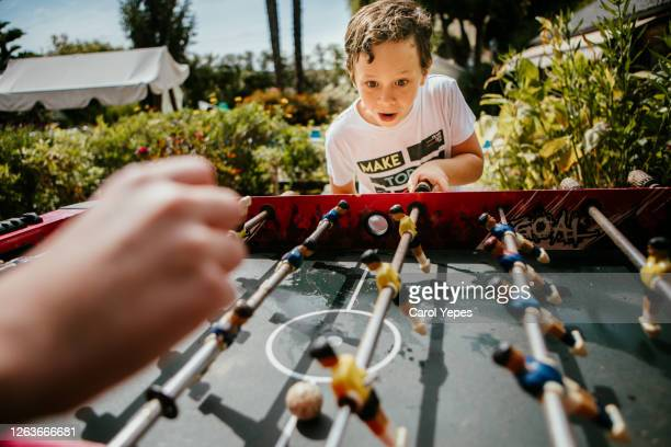 two kids plays football table in back yard in summer.pov - toy stock pictures, royalty-free photos & images