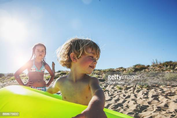 two kids plays  with inflatable ring at beach
