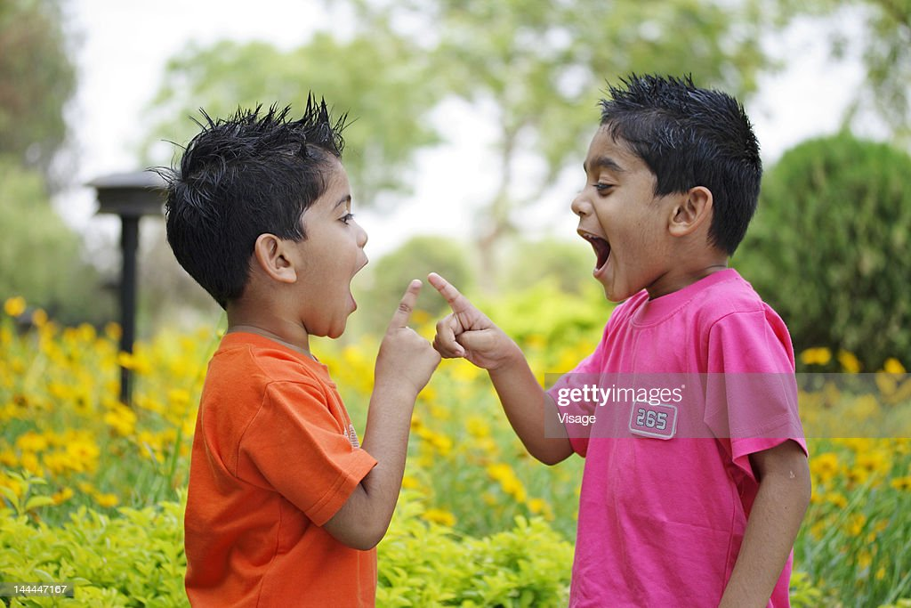 Two kids pointing fingers at each other : Stock Photo