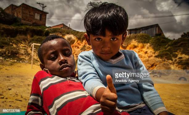 Two kids pose for a photo at a provisional school in Bogota Colombia on November 27 2017 Colombia has one of the largest population of internally...