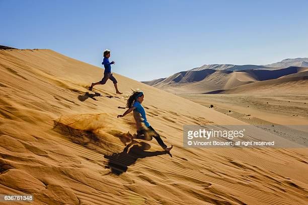 Two kids running down Sossusvlei dunes