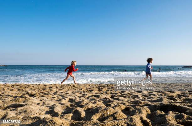 two kids running on beach, barcelona - la barceloneta stock pictures, royalty-free photos & images