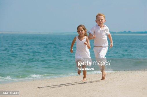 Two Kids Running On Beach Stock Photo