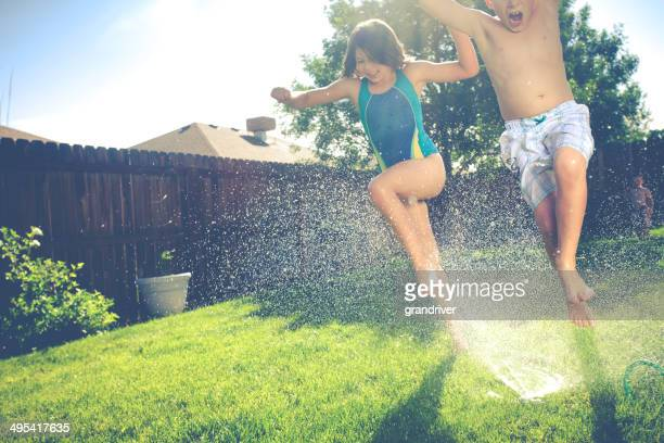 Two Kids Running Through Sprinklers