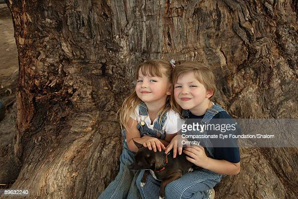 two kids sitting by a tree holding a small dog