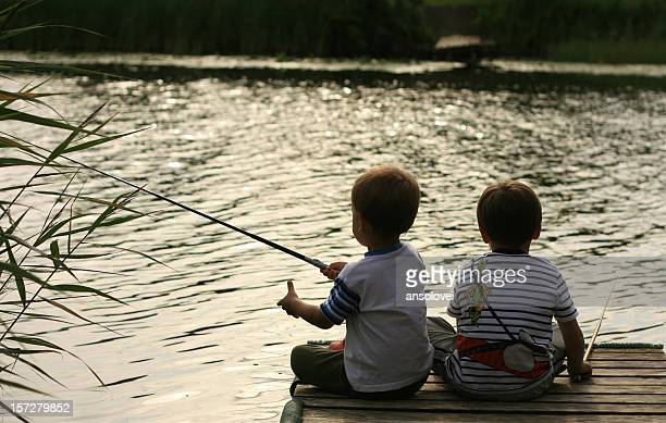Two kids sitting on a dock fishing in the water