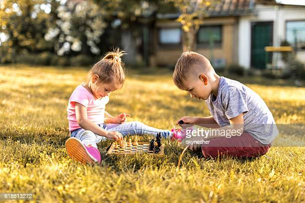 Two kids sitting on the grass and playing chess.