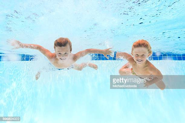 Two Kids Swimming Underwater In A Pool