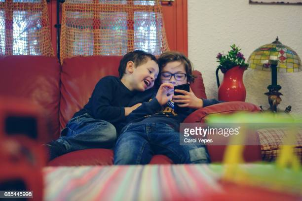 two kids using smartphone at home