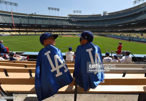 Two kids wait for the start of Los Angeles Dodgers and San Francisco Giants baseball game during batting practice on Opening Day at Dodger Stadium on...