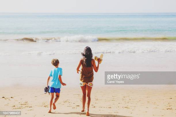 two kids walking down to beach.rear view - algarve stock pictures, royalty-free photos & images