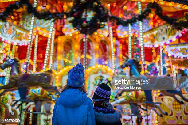 Two kids wearing winter hats and watching a colourful and festive carousel opposite Hampton Court Palace. Back view. Christmas holidays 2013/2014