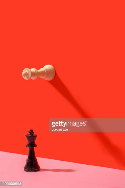 two king chess pieces on a colored background - war and conflict stock pictures, royalty-free photos & images