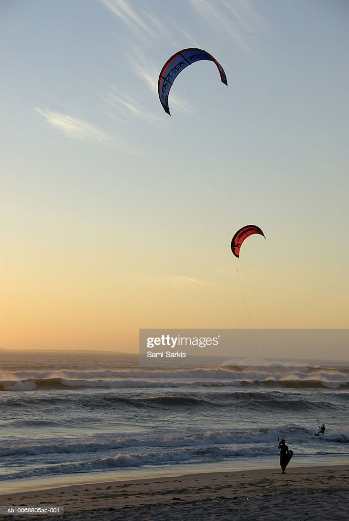 Two kite surfers on beach at sunset : Stock Photo